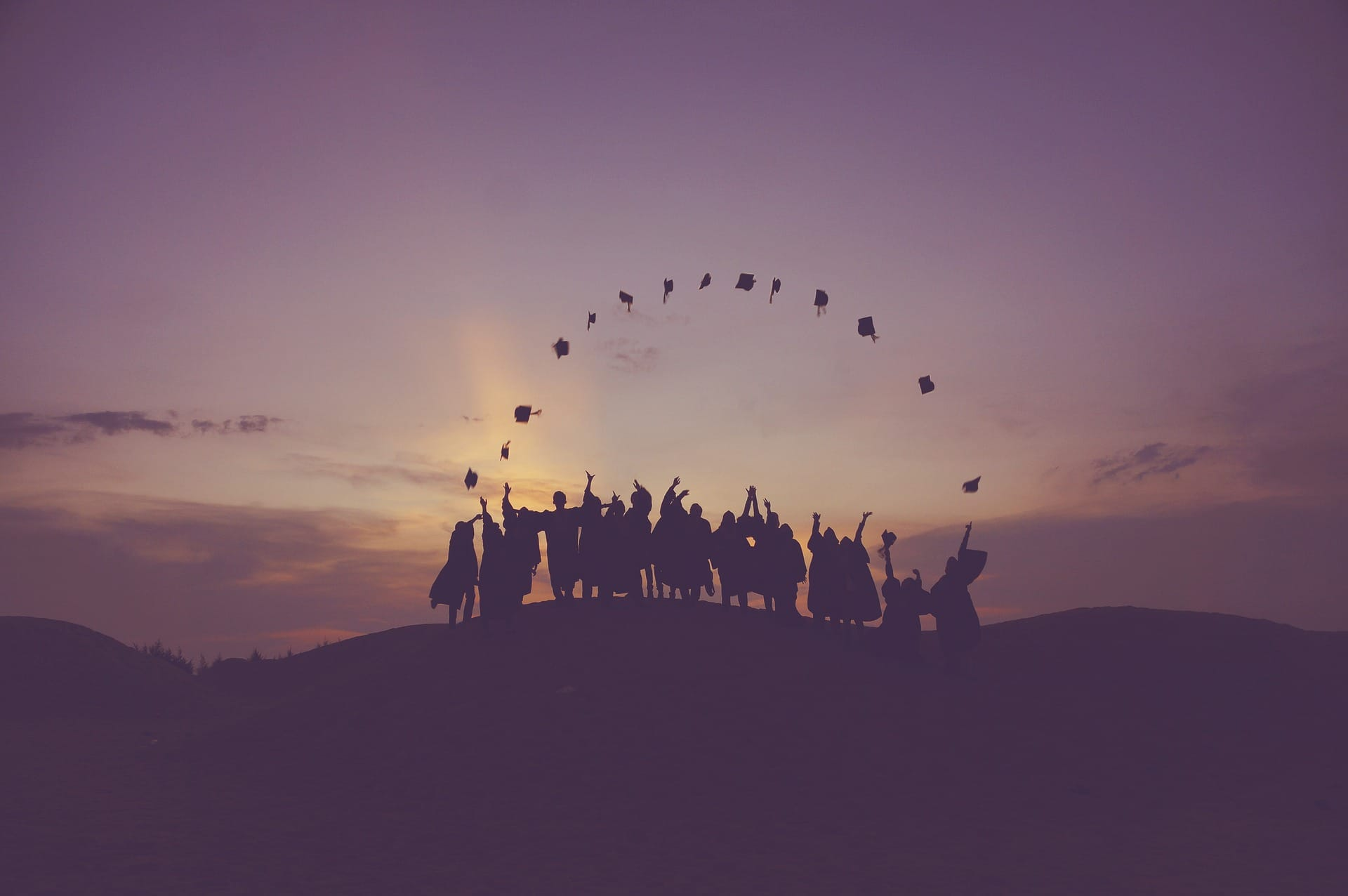 Graduates tossing hats into the air